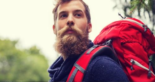 Voici un homme barbu avec son sac à dos sur le dos