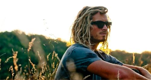 """Voici un barbu blond au """"look"""" surffer profitant du soleil."""