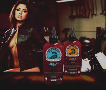 Bossman brands jelly beard oil on a wooden table, 2 scent, magic and gold in front of a Sexy girl with a motorcycle