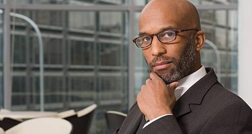 Homme noir qui touche sa barbe au travail